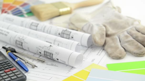 Pricing an architectural drawing blueprint with calculator working gloves and color swatch for painting