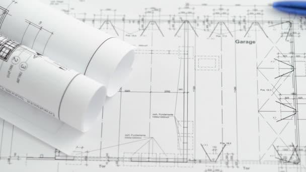 ein Stift rollt über einen Bauplan für Architekturzeichnungen.