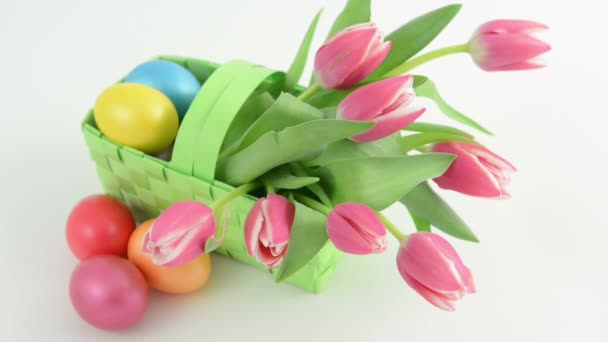 Rack focus of basket with bunch of pink tulips and Easter eggs