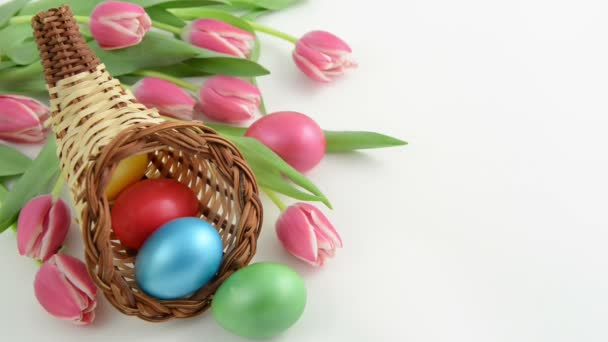 Rack focus of cornucopia basket with bunch of pink tulips and Easter eggs