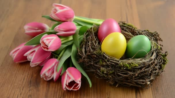 zoom on glass jar with bunch of pink tulips and Easter eggs
