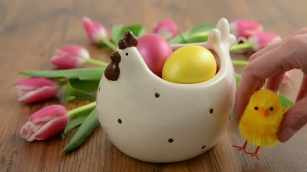 Sitting down chicken aside a chicken cup with easter eggs and tulip bunch