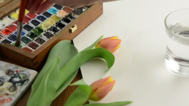 Painting with paintbrush green leaves of tulip in watercolors. Aside a palette.