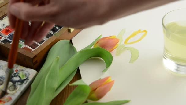 ainting, az ecset orange tulip bud akvarellek és a víz-glass tisztítókefe.