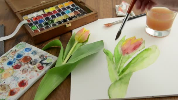 Painting with paintbrush orange tulip bud in watercolors and cleaning the brush in water glass.