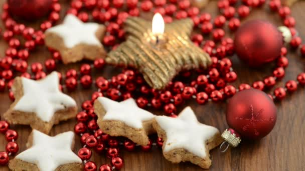 Christmas sweets like cinnamon pastry and candle with red pearls