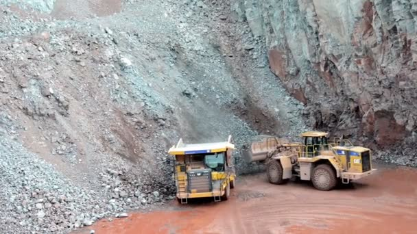 Earth mover ready to loading a dumper truck in a quarry
