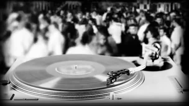 Dj record turntable with blurred dance crowd in background