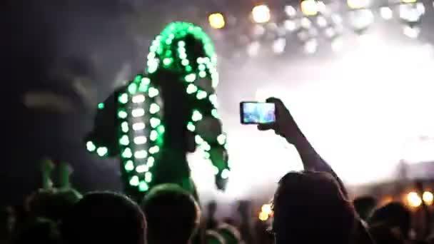obří robot člověka na chůdách se pohybuje mezi diváky festivalu taneční hudby v Barceloně