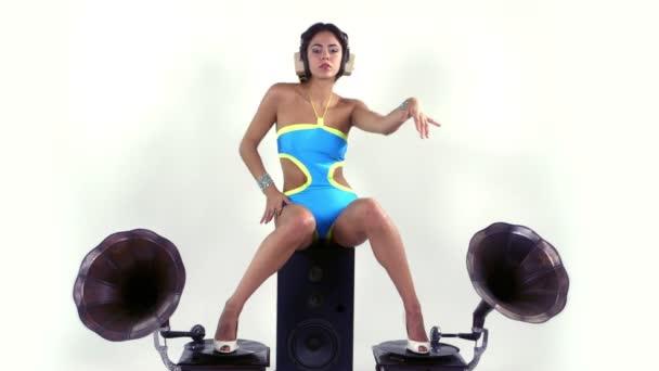 Sexy mladá žena tance a představuje sedící na hifi reproduktor s 2 retro gramofony