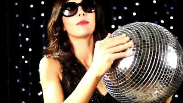 eine supersexy Frau tanzt mit einer Discokugel