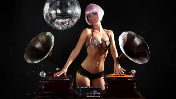 gogo lily malibu schoss tanzend und posierend hinter Grammophon-DJ-Plattentellern