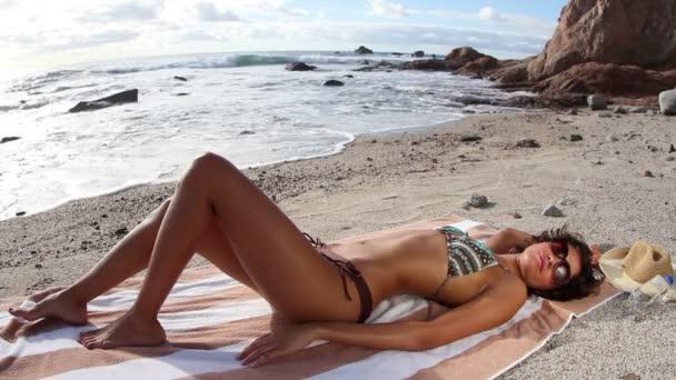A bikini sunbaths a tengerparton a napkelte gyönyörű lány