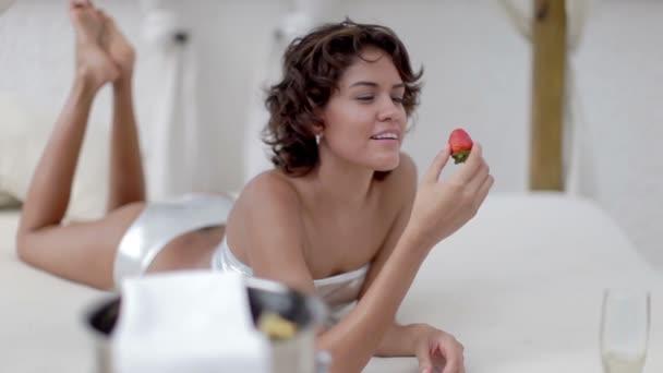 sexy žena v bikinách žere jahody na daybed kolem bazénu