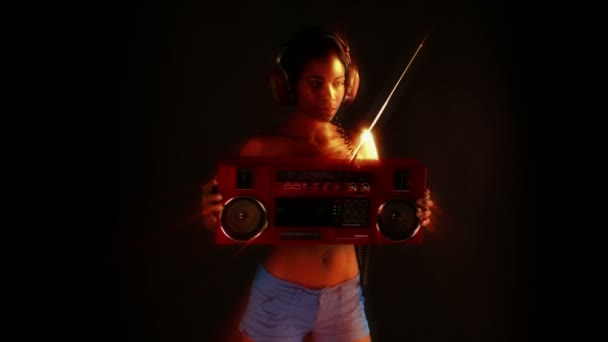 Sexy mladá žena tance a představuje drží retro červená boombox