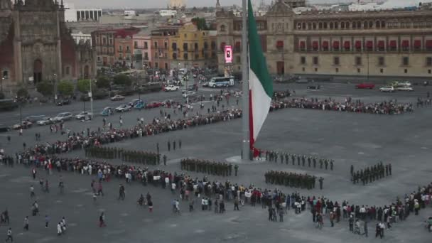 Crowds gather in the zocalo square to watch mexican soldiers take down the flag