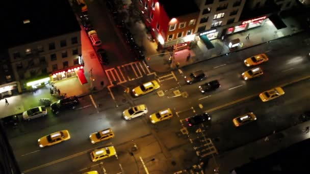 Looking down onto a new york street of fast moving traffic at night