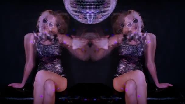 eine sexy Gogo-Tänzerin, die in einem Studio mit einem sich drehenden Discoball tanzt und posiert