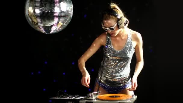 ein sexy weiblicher DJ tanzt und spielt Platten mit Disco-Hintergrund