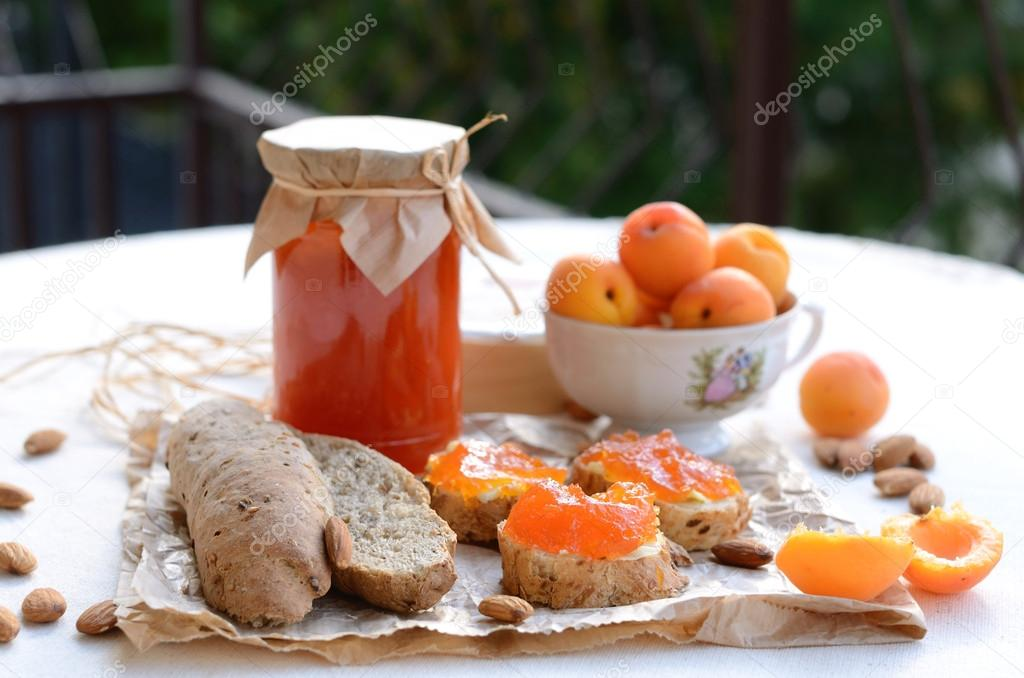 Breakfast with apricot jam, bread, fresh apricots and almonds