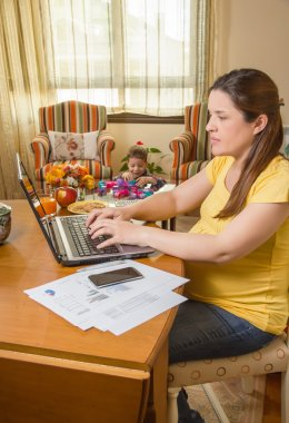 Pregnant mother working in home office with son