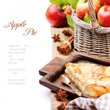 Piece of homemade apple pie with fresh apples in basket