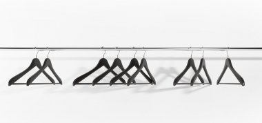 Black clothes hangers on white background