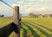 Fotografia una recinzione e una casa in campagna