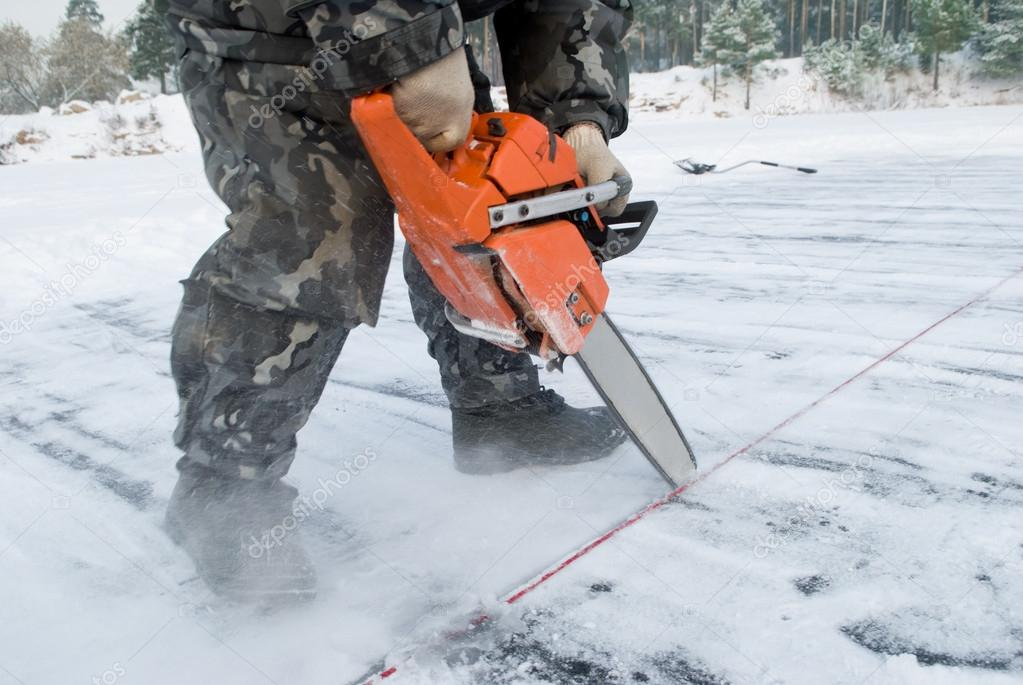 Worker carving out ice on lake