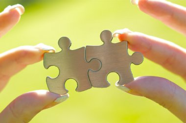 Woman hands holding puzzle pieces