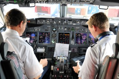 Pilots in the cockpit during a commertial flight stock vector
