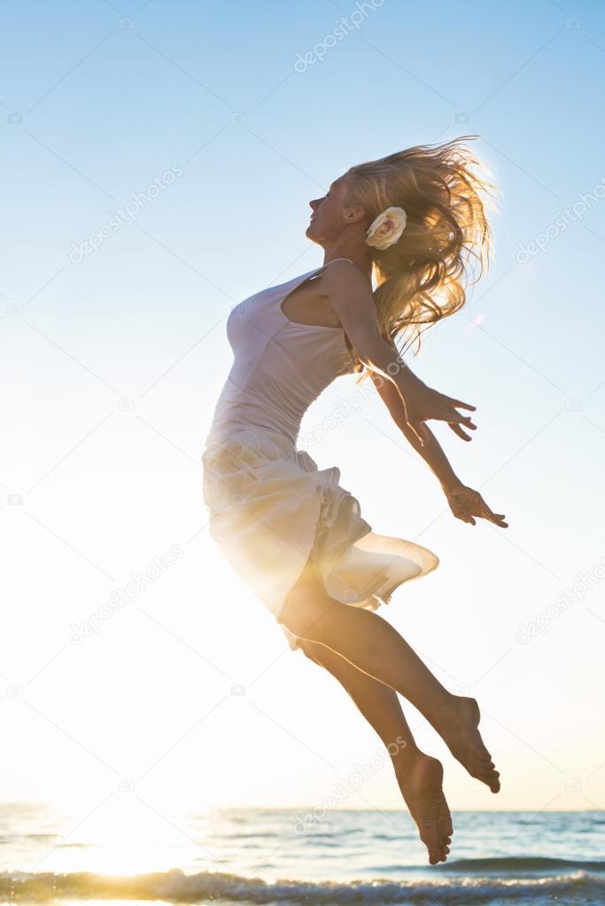 Happy Woman Jumping at the sea