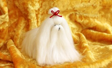 cute Maltese dog toy on yellow background, close-up
