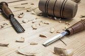 Fotografie oiner nástroje, kladivo a dláto na dřevěné tabulce pozadí