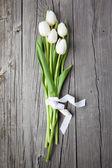 Fotografie Kytice bílých tulipánů na dřevěný stůl