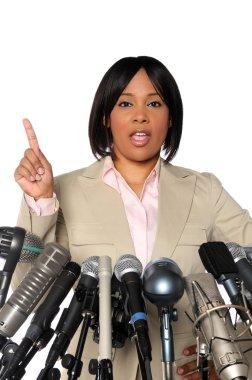Woman Speaking Behind Microphones