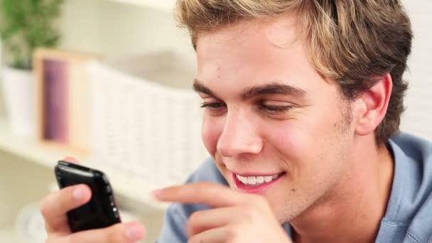 radostné mladý muž pomocí mobilního telefonu textovou zprávu