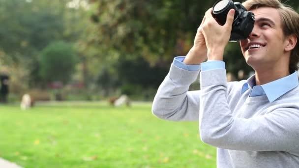 šťastný mladý student relaxační fotografování venku pomocí digitálního fotoaparátu