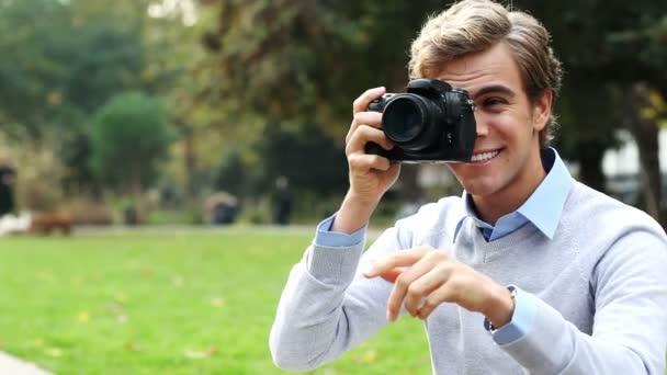 atraktivní mladý muž fotograf pomocí dslr fotoaparát digitální fotografování venku v parku v slunci