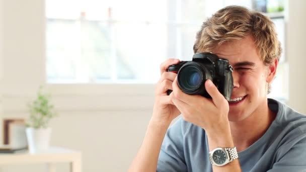 atraktivní mladý muž fotografování s digitálním fotoaparátem dslr doma