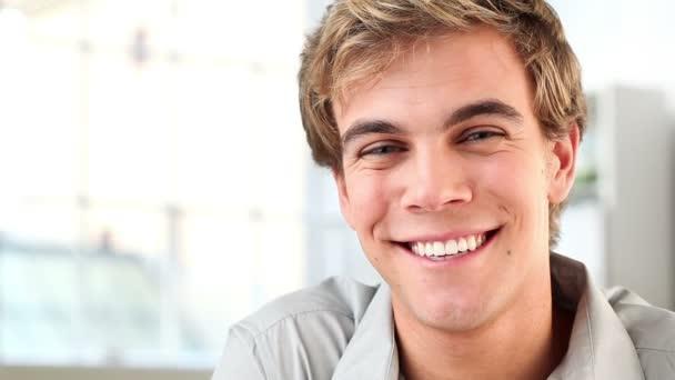 Detailní portrét motivované mladého muže, usmívající se na kameru - doma