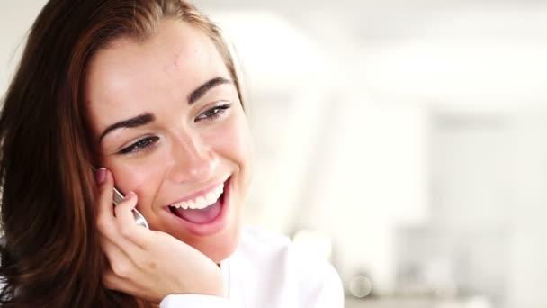 radostné mladá žena mluví na mobilním telefonu doma