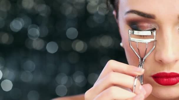 Macro closeup of Sexy young woman wearing make up using eyelash curler has perfect skin