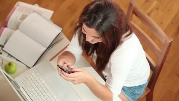 Junge Frau mit ihrem Handy zu Hause