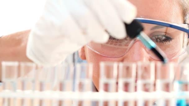 Aranyos orvosi vagy tudományos kutató-vegyész-tudós segítségével a Pipetta és kémcsövek laboratóriumban