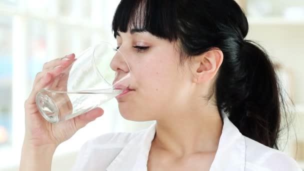 Detailní portrét zdravé mladé ženy s úsměvem pitné vody v domácnosti