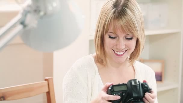 mladá žena držící fotoaparát a prohlíží fotografie na pohovce