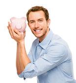 glücklicher junger Mann legt Geld in Sparschwein isoliert auf weiß