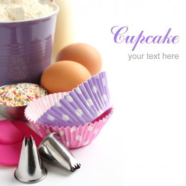 Cupcake cases and ingredients over white with sample text