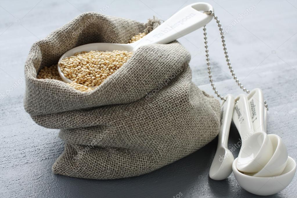 Quinoa grain in small burlap sack and porcelain measuring